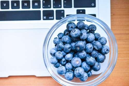 Blueberries in bowl on macbook