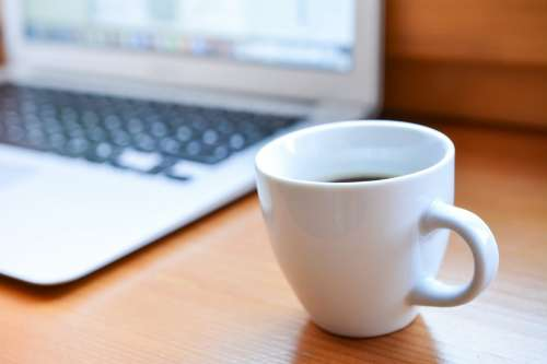 Cup of coffee with macbook in background