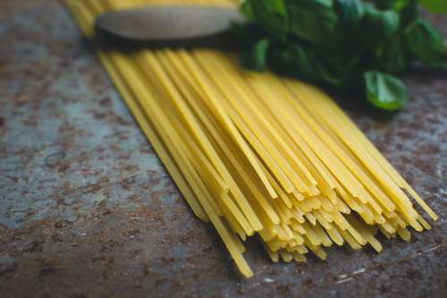 Pasta spaghetti with basil and a wooden spoon