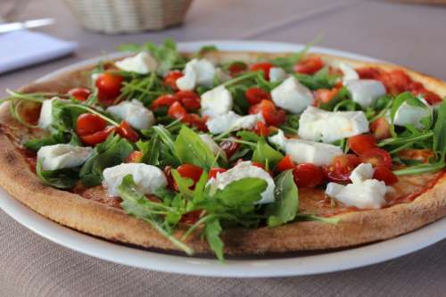 Pizza with rucola, mozzarella and tomatoes