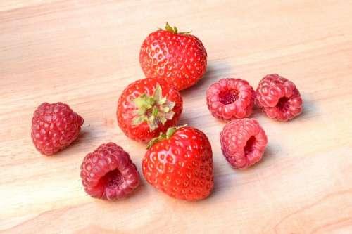 Strawberries and raspberries on wood