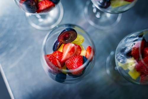 Strawberries, blueberries, plums and grapes in a glass