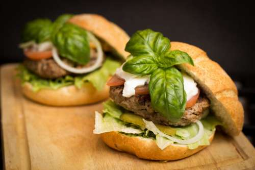 Two burgers with basil