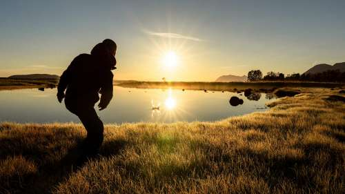 Man Throwing a Stone into a Calm Lake During Beautiful Sunrise