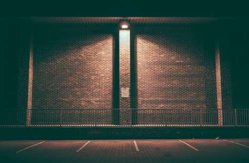 Brick Wall Empty Lighted Night Parking Area