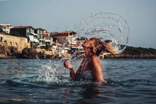 Girl Splashing Hair in the Sea with Mediterranean Background