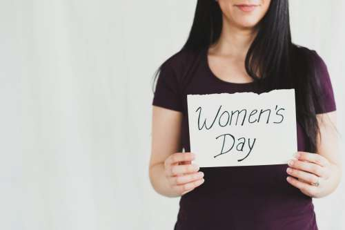 "A Woman Holds 'Women's Day"" Sign Photo"
