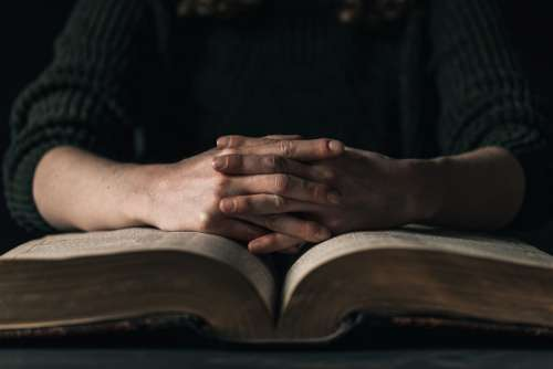 Hands Resting On Open Book Photo