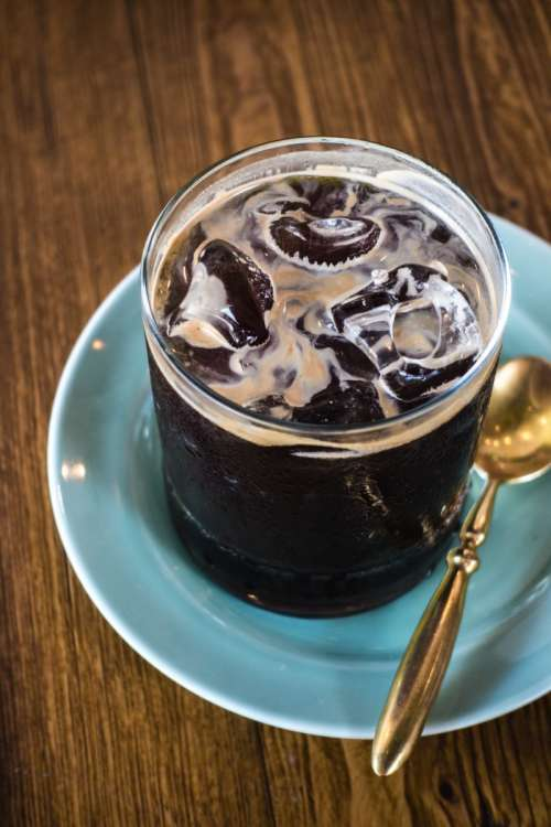 Iced black coffee with golden spoon