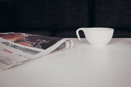 Cup of coffee and a newspaper on the table