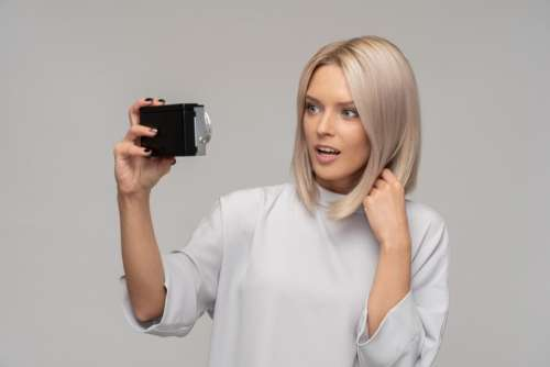 Surprised Woman Taking A Selfie With An Old Camera