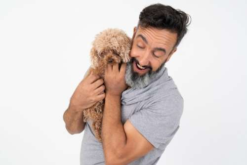 Contented Mature Man Holding A Puppy