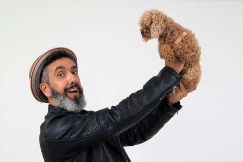 Impressed Mature Man Holding A Puppy