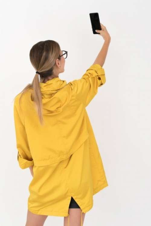 Young Blonde Woman In Yellow Raincoat And Black Glasses Taking A Selfie