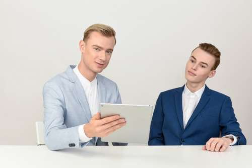 Two Male Colleagues Looking At Tablet And Talking About Work
