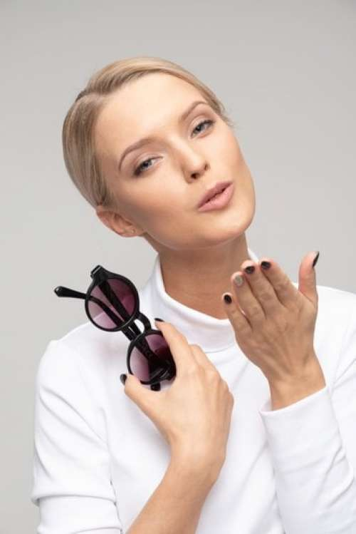 Young Attractive Woman Holding Sunglasses And Sending An Air Kiss