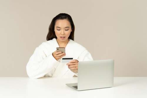 Young Asian Woman Using Phone And Checking Card