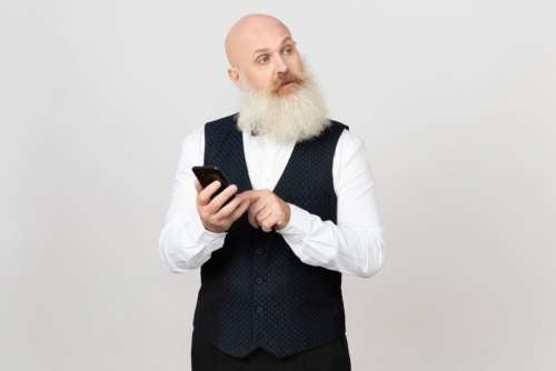 Aged Man Holding Phone And Looking Aside
