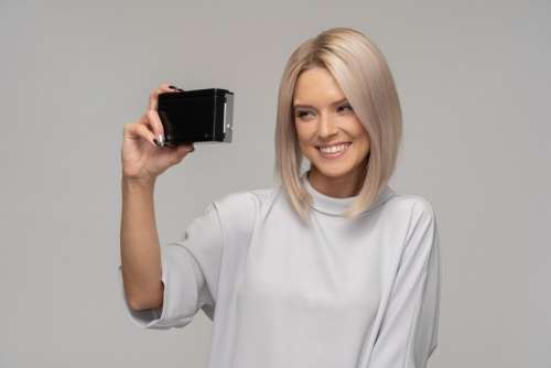 Smiling Young Woman Taking A Selfie With An Old Camera