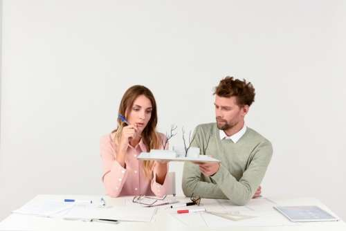 Female And Male Architects Discussing The Scale Model Of A House