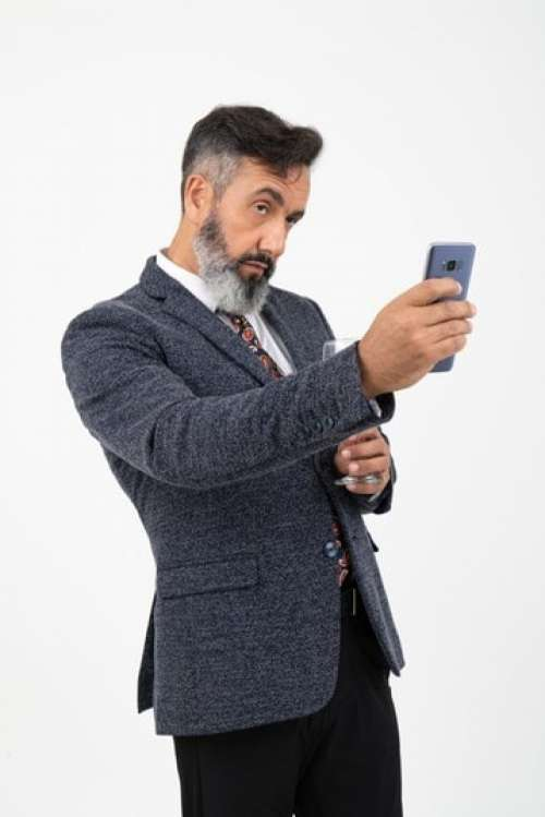 Man In Suit Holding His Phone Like Doing A Photo