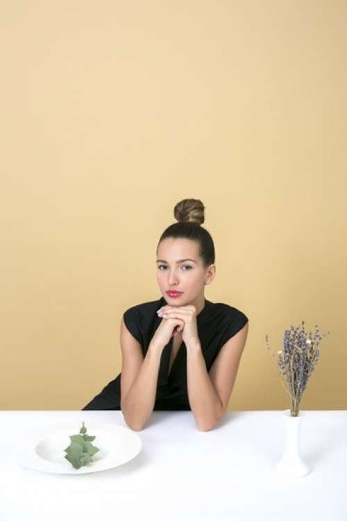 Elegant Young Woman Sitting At The Table