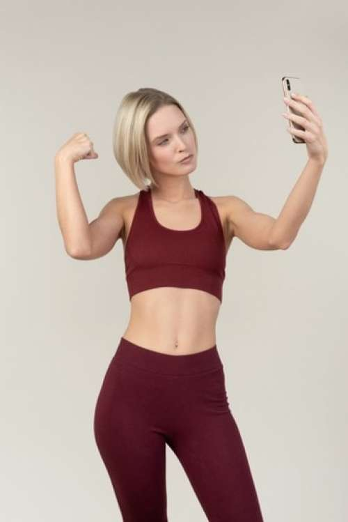 Young Woman In Sportswear Showing Muscles And Making A Selfie