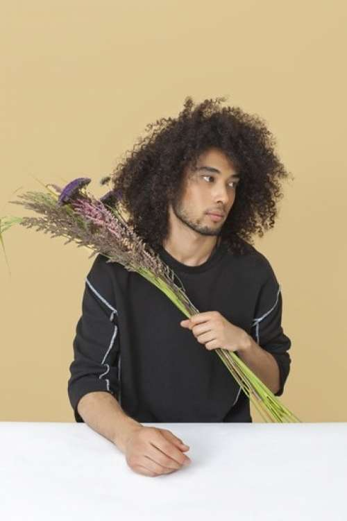 Young Man Holding A Bouquet Of Dried Flowers