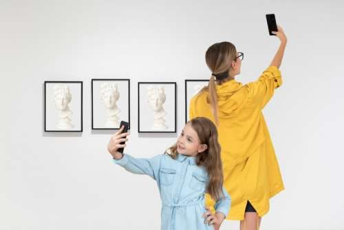 Mother And Daughter Making Selfies In Art Gallery