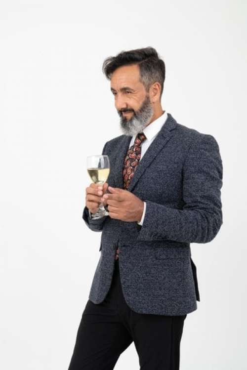 Man In Suit Slightly Smiling And Holding A Glass