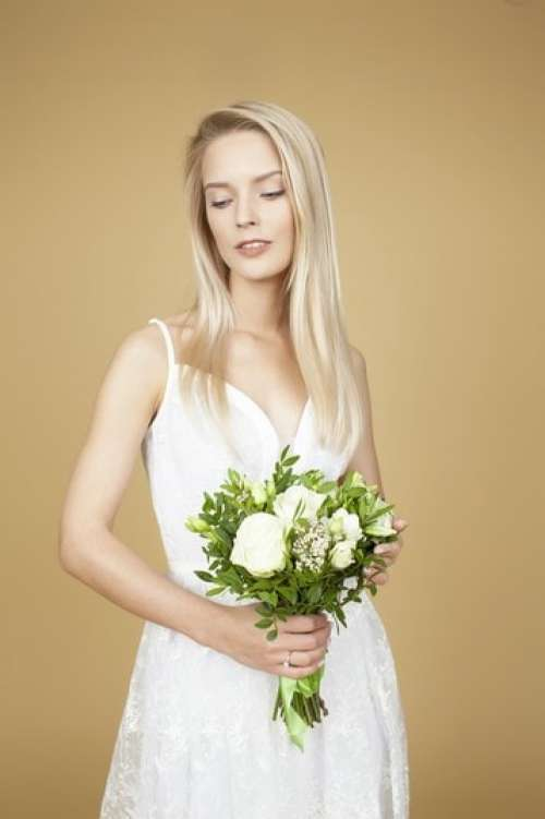 Beautiful Bride Holding A Wedding Bouquet Of White Flowers