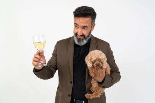 Man With A Dog Holding A Glass Of Wine