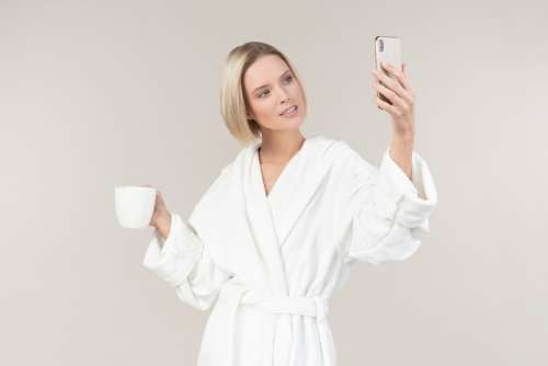 Young Girl Holding Mug And Smartphone