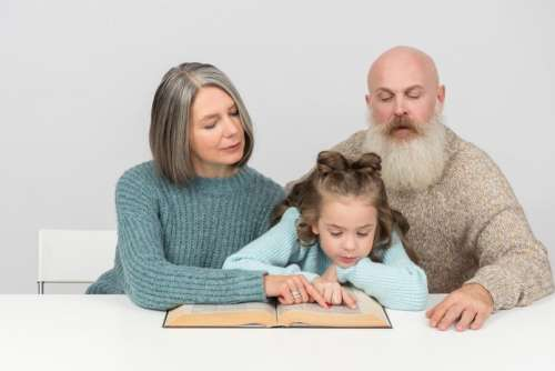Grandparents And Kid Girl Granddaughter Reading A Book