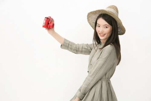 Gir In Hat Standing In Profile And Making A Selfie With Red Camera