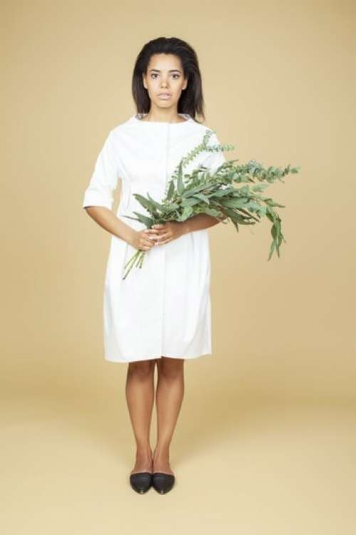 Young Woman In White Dress Holding A Plant Bouquet