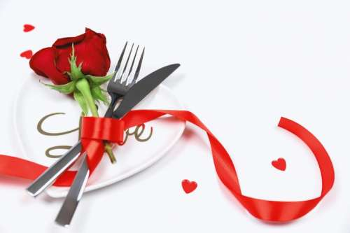 Fork, knife and spoon with red rose on white table. Love concept