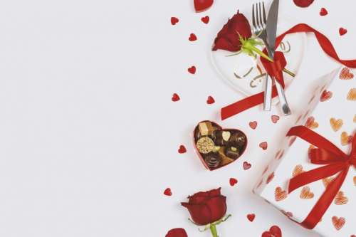 Valentine's Day. Roses, hearts, gift box, plate with cutlery and box of chocolate on white background.