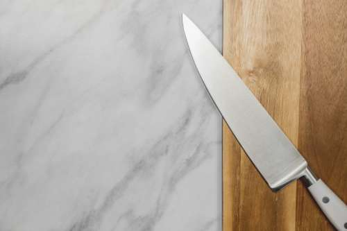 Big kitchen knife lying on an old cutting board