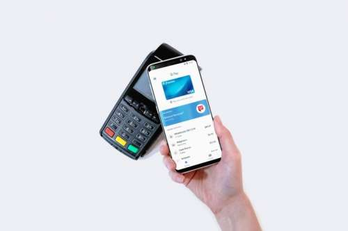 Hand with a smartphone making a payment on a Pay terminal on white background