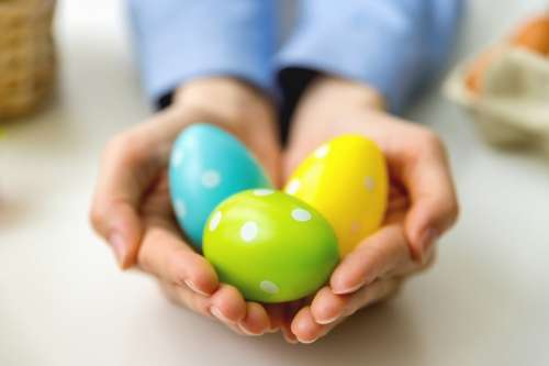 Woman's hands holding modern painted easter eggs.