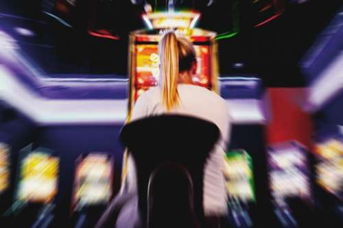 Blurred background of person in casino playing slot machine