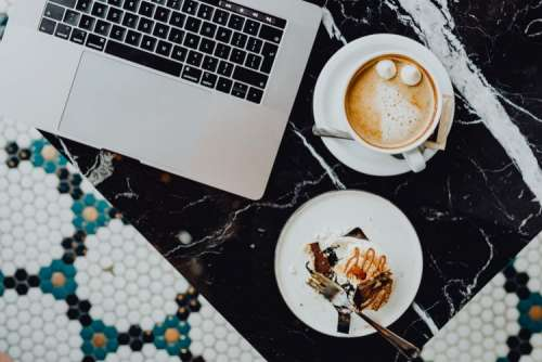 Laptop, coffee and cake with meringue and whipped cream on black marble