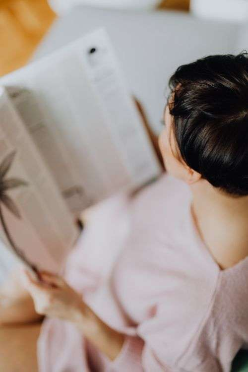 A woman with short dark hair reads a newspaper