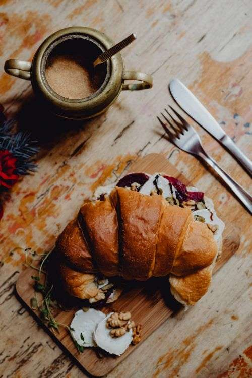 Croissant with goat cheese, beetroot and a cup of coffee for breakfast