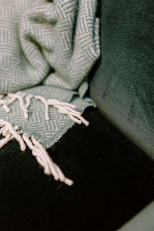 Pastel green blanket on a velour dark green armchair