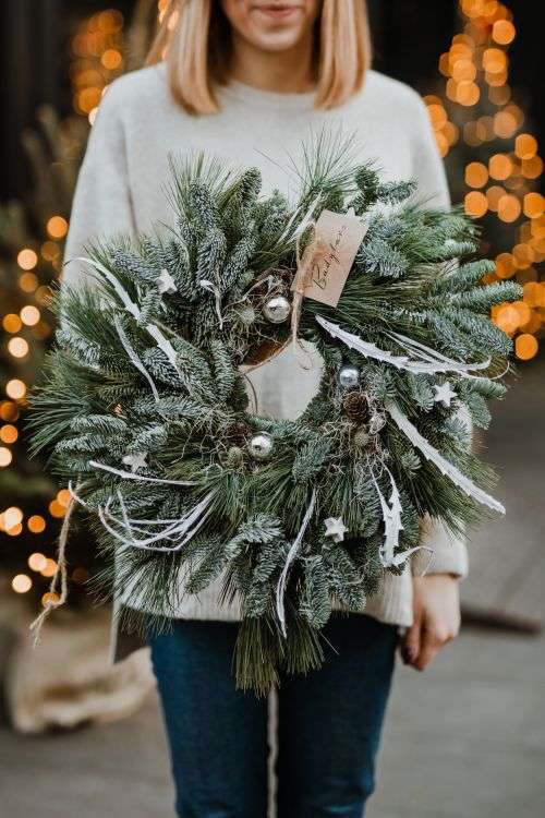 The woman is holding a Christmas wreath in her hands