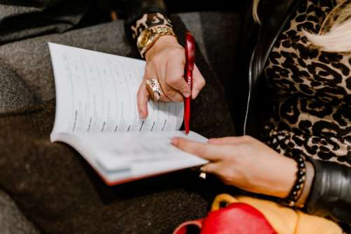 A woman with a large ring and a golden watch writes down in the calendar