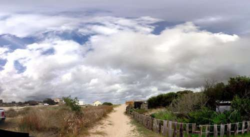 road sand fence clouds sky