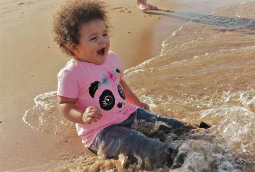 child ocean seashore beach ocean wave